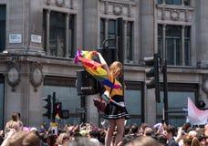 De vrouw beklimt op het verkeerslicht bij het Circus van Oxford, Londen, om een betere mening van Vrolijk Pride Parade te krijgen stock foto's