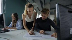 De vrouw benadert de mens bij computer en verklaart zijn werk naast een vrouw die op hoofdtelefoon spreken en op een toetsenbord  stock videobeelden