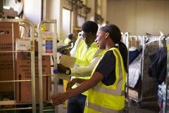 De vrouw bereidt broodjeskooi voor levering voor, door supervisor wordt gecontroleerd die Royalty-vrije Stock Foto's