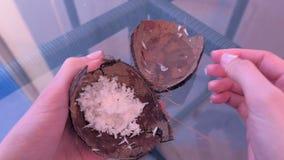 De vrouw bereidt gezichtsmasker van het verse kokosnoot scheren en water voor mengt het in shell stock videobeelden