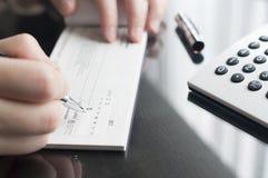 De vrouw bereidt het schrijven van een controle voor Royalty-vrije Stock Fotografie