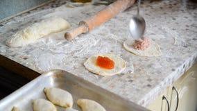 De vrouw bereidt pastei met jam en vlees voor stock video