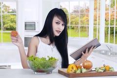 De vrouw bereidt salade voor terwijl het lezen van boek Stock Foto