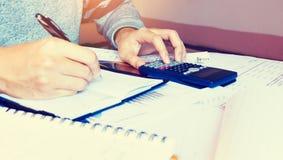 De vrouw berekent financiën op bureau met het analyaing van rapport bij Stock Afbeeldingen
