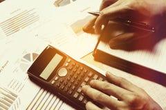 De vrouw berekent financiën op bureau met het analyaing van rapport bij Royalty-vrije Stock Fotografie