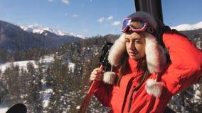 De vrouw berijdt de cabine van de lift bij een skitoevlucht genietend de winter van aard door het venster van de gondel stock video