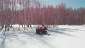 De vrouw berijdt een vierlingfiets op het sneeuwgebied op de achtergrond van een berkbos stock videobeelden