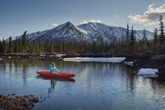 De vrouw berijdt kano op meer op berggebied in de lentetijd royalty-vrije stock fotografie