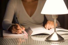 De vrouw bestudeert en neemt nota's laat bij nacht Royalty-vrije Stock Fotografie