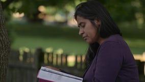 De vrouw bestudeert in openlucht Bijbel in Binnenplaats stock videobeelden