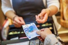De vrouw betaalt in contant geld met euro bankbiljetten royalty-vrije stock afbeeldingen