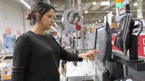 De vrouw betaalt jat creditcard voor betaling bij zelfcontrole