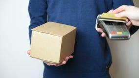 De vrouw betaalt met NFC-technologie op een smartphone en het ontvangen van pakket van de leveringsmens stock video