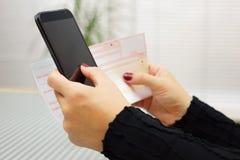 De vrouw betaalt rekening op mobiele slimme telefoon stock fotografie
