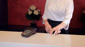 De vrouw betaalt voor hotel gebruikend smartphone, geeft de receptionnist elektronische sleutel 4K stock footage