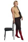 De vrouw bevindt zich, leunend over een stoel. royalty-vrije stock afbeelding