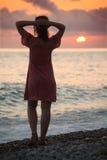 De vrouw bevindt zich op zeekust op zonsondergang, achtermening royalty-vrije stock fotografie