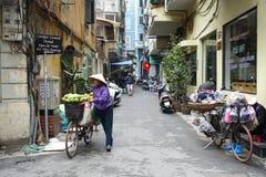 De vrouw beweegt een fiets op straat stock foto's