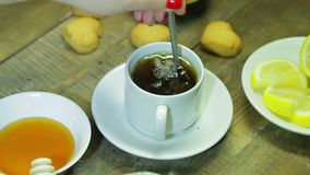 De vrouw beweegt in lepel in witte kop op houten lijst Vers gebrouwen zwarte thee stock footage