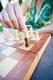 De vrouw beweegt stuk in schaak Royalty-vrije Stock Afbeeldingen
