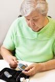 De vrouw beweegt teststrook in de glucosemeter Stock Foto's