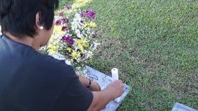 De vrouw bezoekt de kaars van Grafzerkaanbiedingen bij Begraafplaats stock footage
