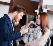 De vrouw bidt haar vriend om haar voor te stellen een kleding Stock Foto
