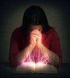 De vrouw bidt over een Bijbel Stock Foto