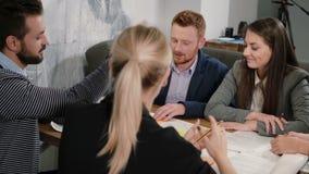 De vrouw biedt goed idee aan iedereen gelukkig is, hoog-fiving elkaar Creatieve commerciële teamvergadering in startbureau stock video