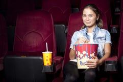 De vrouw bij de bioskoop eet popcorn Royalty-vrije Stock Afbeeldingen