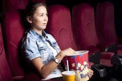 De vrouw bij de bioskoop eet popcorn Stock Foto's