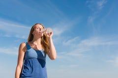 De vrouw bij hemelachtergrond drinkt in openlucht water royalty-vrije stock foto's