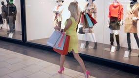 De vrouw bij het winkelen, jong modieus meisje met vele pakketten loopt voorbij manierboutiques met ledenpoppen terwijl aankopen  stock video