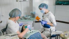 De vrouw bij tandartskliniek brengt tandbehandeling ertoe om een holte in een tand te vullen Tandrestauratie en samengesteld mate stock afbeelding