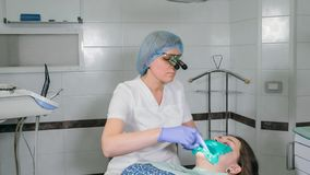De vrouw bij tandartskliniek brengt tandbehandeling ertoe om een holte in een tand te vullen Tandrestauratie en samengesteld mate royalty-vrije stock fotografie