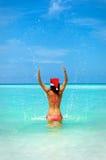 De vrouw in bikini bespat water in turkooise overzees stock afbeeldingen
