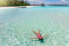 De vrouw in bikini drijft op het turkooise, tropische overzees van de Maldiven royalty-vrije stock foto's