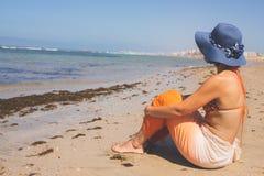 De vrouw in bikini is op vakantiezitting op het strand in de zomer royalty-vrije stock fotografie