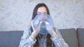 De vrouw blaast een grote bel van een blauw slijm op Spel met slijm stock videobeelden