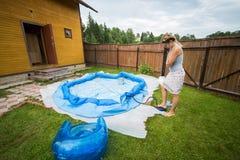 De vrouw blaast opblaasbaar zwembad op stock afbeeldingen