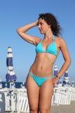 De vrouw in blauw zwempak bevindt zich op strand Royalty-vrije Stock Foto