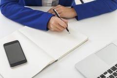 De vrouw in blauwe blazer neemt nota's bij een lijst Royalty-vrije Stock Fotografie