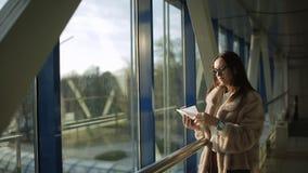De vrouw in de bontjas bij de luchthaven bij het venster in het laatste licht van de zon kijkt op de baan in anticiperen stock video