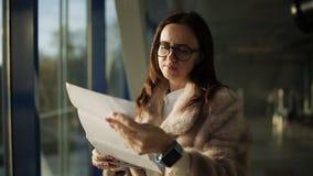 De vrouw in de bontjas bij de luchthaven bij het venster in het laatste licht van de zon kijkt op de baan in anticiperen stock videobeelden