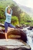 De vrouw in de boom van Vrikshasana van yogaasana stelt in openlucht bij waterval Royalty-vrije Stock Foto
