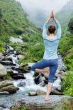 De vrouw in de boom van Vrikshasana van yogaasana stelt in openlucht bij waterval Stock Afbeelding