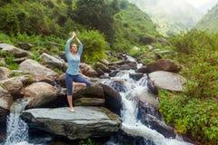 De vrouw in de boom van Vrikshasana van yogaasana stelt in openlucht bij waterval Royalty-vrije Stock Fotografie