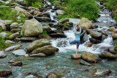 De vrouw in de boom van Vrikshasana van yogaasana stelt in openlucht bij waterval royalty-vrije stock foto's