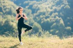 De vrouw in Boomyoga stelt het Dragen van Algemene Jumpsuit buiten Uitoefenend stock foto's