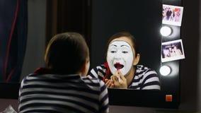 De vrouw bootst lippenstift in de spiegel na stock videobeelden